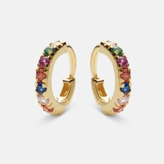 Gently hugging the ear lobe these classic hoops are embellished with colored gemstones all around. An elegant everyday style. Composition: Sterling silver(925), 18 carat gold plated, polished finish. Cubic zirkonia. Item number: 9337 a.