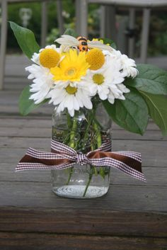 """Bright Gerber Daisy, Classic White Daisy, and Billy Balls were mounded together with a busy bee accent for a """"Bay-Bee"""" themed shower"""