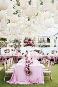 Pink wedding decor| pink table cloths with matching flower arrangements. The white hanging lanterns add a whimsical and romantic feel to the venue|http://www.jardinweddings.com/pretty-in-pink-2