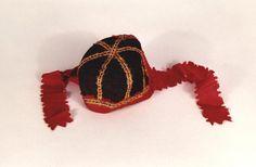 Die Kinderhaube für Jungen besteht aus schwarzer, broschierter Seide mit aufgenähten Goldlitzen und weinroten Bändern und Einfassungen. Sechsteilig genäht. Die Haube stammt angeblich aus Holstein.