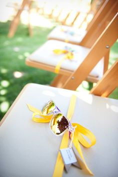 sunglass favors tied with ribbon to chairs at wedding ceremony