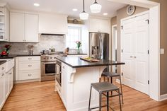 Kitchen remodel by Sicora Design Build: white cabinets, wood floors, center island