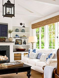Bamboo shades and a sisal rug bring an organic look to this living room and add texture to the crisp, white space. A white painted ceiling with exposed trusses give the room a cozy architectural style, as do built-ins surroun