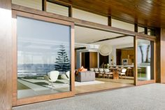 Have a Perfect Exterior Design at Home through Installing Wooden Framed Sliding Patio Doors: Luxurious Beach Residence Exterior With Large Wooden Frame Sliding Glass Doors