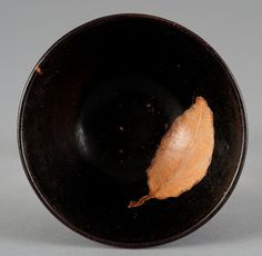 A JIZHOU LEAF-DECORATED BROWN-GLAZED CONICAL BOWL                          SONG DYNASTYThe center of the interior decorated with a translucent leaf of yellowish-buff color reserved against the dark brown matte glaze that thins to russet on the rim and stops above the shallow ring foot to expose the pale stoneware body.