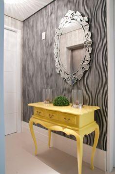 No hall de entrada, bem em frente ao elevador social, Francine dispôs o tradicional conjunto aparador e espelho. aproveitando-se do móvel que pertencia à proprietária, em madeira escura. A arquiteta sugeriu aplicar laca na cor amarela como acabamento, recuperando e modernizando a peça. Combinou um espelho veneziano sobre o papel de parede zebrano.