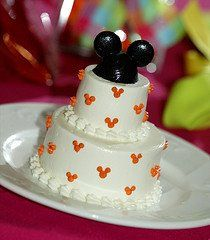 Simple two tier Disney Mickey ears wedding cake with small orange accent Mickey ears