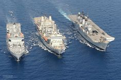 Three Royal Navy ships take part in a Replenishment at Sea or RAS. From left RFA Fort Austin, RFA Fort Victoria and HMS Illustrious are pict...