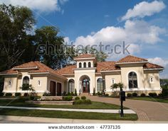 One story stucco residential home with a red clay tile roof and side garage. by Lindasj22, via Shutterstock