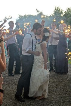 Epitome of my dream wedding. Small crowd, sparklers, suspenders, rolled up sleeves, simple dress, flower in hair. Perfection!
