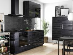 A small black kitchen with doors and drawers in black wood effect combined with glass-doors in smoked tempered glass.
