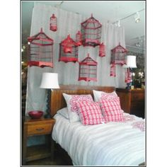 Various shapes of Birdcages all painted red & displayed in a Bedroom setting. Birdcage ideas