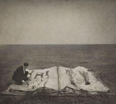 Robert and Shana ParkeHarrison - Book of life, 2000 -  Book of Life shows a man perched on an oversized open book, laying out plants on its pages. The man is wearing a full suit and tie—a representation of the modern industrial world. He seems to be perplexed by his own existence in this environment as well as with the transformation of the book back into the natural world.