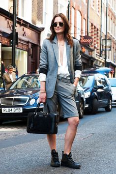 This street style stunner shows us a unique take on the pants suit that would make a super cool statement at any creative office. She masterfully layers a jacket and knee-length shorts over a sexy low-cut silk blouse and accessorizes the masculine look with a tote bag and casual leather hi-top Converse sneakers.