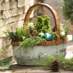 Winter Greenery Basket with Ornaments Plants don't have to be potted to supply your outdoors with picturesque charm. Try grouping together a few seasonal items, such as pinecones, bits of greenery, and some leftover ornaments. Leave the basket by the front door, or put one container on each of your entryway steps.
