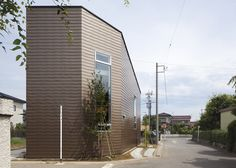 This house in Saitama, Japan, by architects SNARK and OUVI has bronze-coloured walls and a terrace cut out from the roof.  The three-storey residence is located on a small corner plot. The architects added tall narrow windows to three elevations. The first and second floors are set back from the windows, creating triangular lightwells that let daylight through the building. http://www.dezeen.com/2013/03/27/house-in-keyaki-by-snark-and-ouvi/