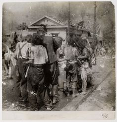 Dazed survivors huddle together in the street ten minutes after the atomic bomb was dropped on their city, Hiroshima, 1945