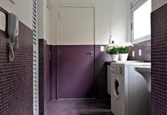 Moderna, a lavanderia recebeu pastilhas de vidro roxas no piso e na metade das paredes. Para dar continuidade, a porta é pintada dessa cor na mesma altura