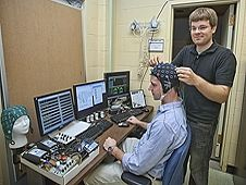 Chad Stephens fixes sensors to the head of colleague Kyle Ellis to measure brain activity during a test of the Multi-Attribute Test Battery software.
