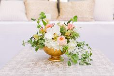 The centerpieces will have gold compotes or clear rectangular vases filled with white hydrangeas, white spirea, blush garden roses, white peonies, blush spray roses, and white ranunculus in the center of each table.