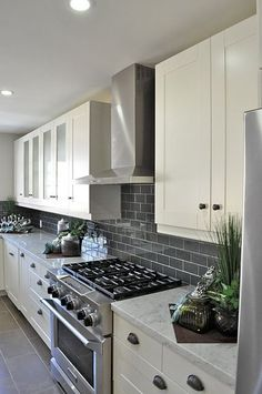 Gray tile backsplash drawing attention to beautiful white cabinetry with alternating solid and glass doors