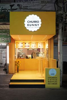 This bright yellow facade highlights a small takeaway café that sells mainly drinks and churros, located in Seoul, South Korea.