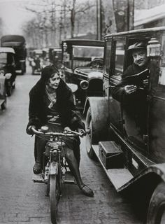 Young woman on a motorcycle asking a chauffeur for directions, Paris, France 1930.