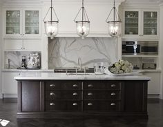 Marco Meneguzzi - kitchens - marble, backsplash, marble, countertops, espresso, stained, kitchen island, white, glass-front, kitchen cabinets, sink in kitchen island, polished nickel, bridge kitchen faucet, herringbone, wood, floors, glass, pendants,