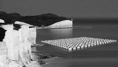 """""""Albion"""" is a land art proposal. A monumental square pattern of white shipping containers is let afloat at the foot of Dover's cliffs. Moved by the waves, the installation aimes to create an abstract relief."""