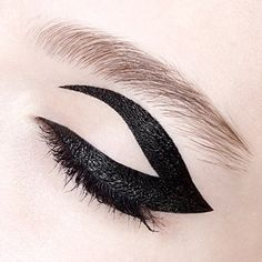 How to get a graphic winged eye using black velvet liner: Color in your full lid with liner, finish with a winged shape on the outer corner. After it dries, use makeup remover to create the negative space design.