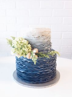 Blue ombré ruffle wedding cake with small arrangement of green hydrangeas, caspias, and pale pink snapdragons.
