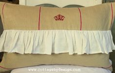 "Tan and cranberry striped pillow with embroidered crown detail and 4"" ruffle in soft white linen. $50 for case only. $58 with down and feather insert. Measures 14 x 23. Zip closure."