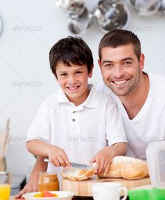 Smiling father and son preparing a toast ...  bowl, boy, breakfast, caucasian, cheerful, child, childhood, children, chocolate, color, domestic, drink, eating, enjoyment, family, father, food, fruit, fun, happiness, happy, healthy, home, horizontal, house, indoors, jam, juice, kitchen, life, looking, love, man, men, nutritive, orange, parents, people, sitting, smile, son, table, toast, together, togetherness, young