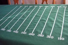 easy DIY tablecloth #superbowl  perhaps with green plastic table cloth, tape and stickers? would be funny with team names on either end.