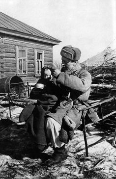 A Red Army soldier feeds a baby he has found abandoned in an empty hut in the village of Izvekovs Smolensk Region March 14 1943.