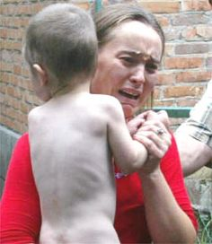 A woman carrying a child cries after being released as part of the hostages released Thursday before the explosions and shootings.