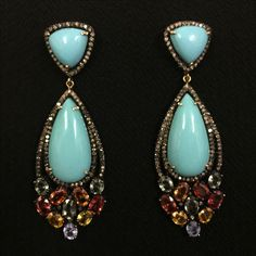 Turquoise, Sapphire & Diamond Earrings. Accompanied by 31.90 carats of Turquoise, 10.60 carats of Sapphire, & 1.95 carats of Diamonds. Set in 14 karat Gold.