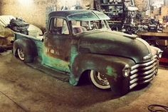 Chevy rat rod bagged rusted on white walls