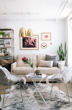 modern chic living room with sheepskin chairs and gold light pendants.