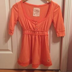 Hollister top Orange Hollister top perfect for spring! Light weight material - 60% cotton and 40% polyester. Slight pilling in the underarm area (picture 3) but could definitely be removed with a razor! Top is fitted and torso area is flowy. Very good condition besides the pilling - no stains or rips! Hollister Tops