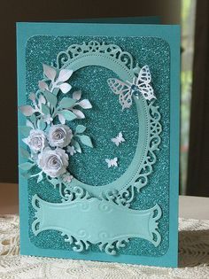 Turquoise glitter paper, mini royal roses, leafy branches, fancy labels, floral oval.