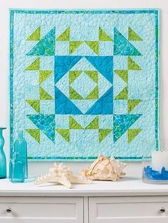 """Bring the feel of cool island breezes to your next luncheon by topping your table with this fresh, tropical quilt. The complete instructions include layout diagrams and fabric suggestions. Finished size is 24"""" x 24""""."""