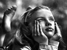 Zij staart vanuit het keukenraam ziet niets, maar toch kijkt ze Regendruppels glijden langs ´t glas naar benee en op de achtergrond galmt de reclame op TV Ver weg verzonken in haar gedachten hoort …
