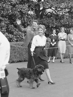 """President Ronald Reagan and first lady Nancy Reagan walk toward the White House in Washington, with their dog """"Lucky,"""" a Bouvier des Flandres."""