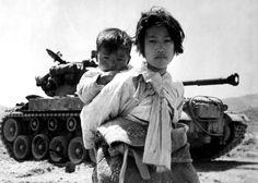 With her brother on her back a war weary Korean girl tiredly trudges by a stalled M-26 tank, at Haengju, Korea. June 9, 1951. (U.S. Navy/Maj. R.V. Spencer, UAF)