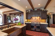Spanish Colonial Kitchen with carved cabinets | Hamilton-Gray Design. Inc.