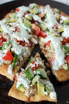 Fresh homemade greek pizza with greek yogurt, garlic, chicken, cucumber, avocado and feta cheese.