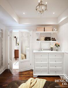 walk in closet, dream closet, white cabinetry, parisian chic, open shelving, pretty chandelier, walnut floors, tufted ottoman