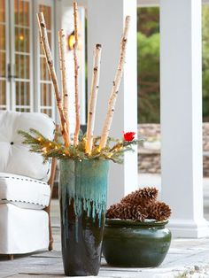 Pinecone and Birch Winter Containers  White birch logs and evergreen branches add a festive touch to a tall garden container, an ideal holiday decoration for your front porch. A container of large pinecones offsets the tall decoration, and a small string of lights and a faux red bird finish the holiday display.