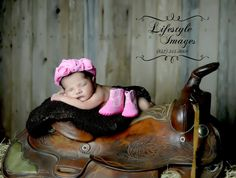 In this picture taken by Lifestyle Images Photography, the sleeping baby girl lays comfortably atop a prop blanket on a western saddle. This was taken in the studio with the fence background. Lifestyle Images Photography, Conroe Texas, Montgomery County, The Woodlands, Montgomery, Magnolia, Willis, Spring, Humble, Houston, infant, baby, professional indoor photography session